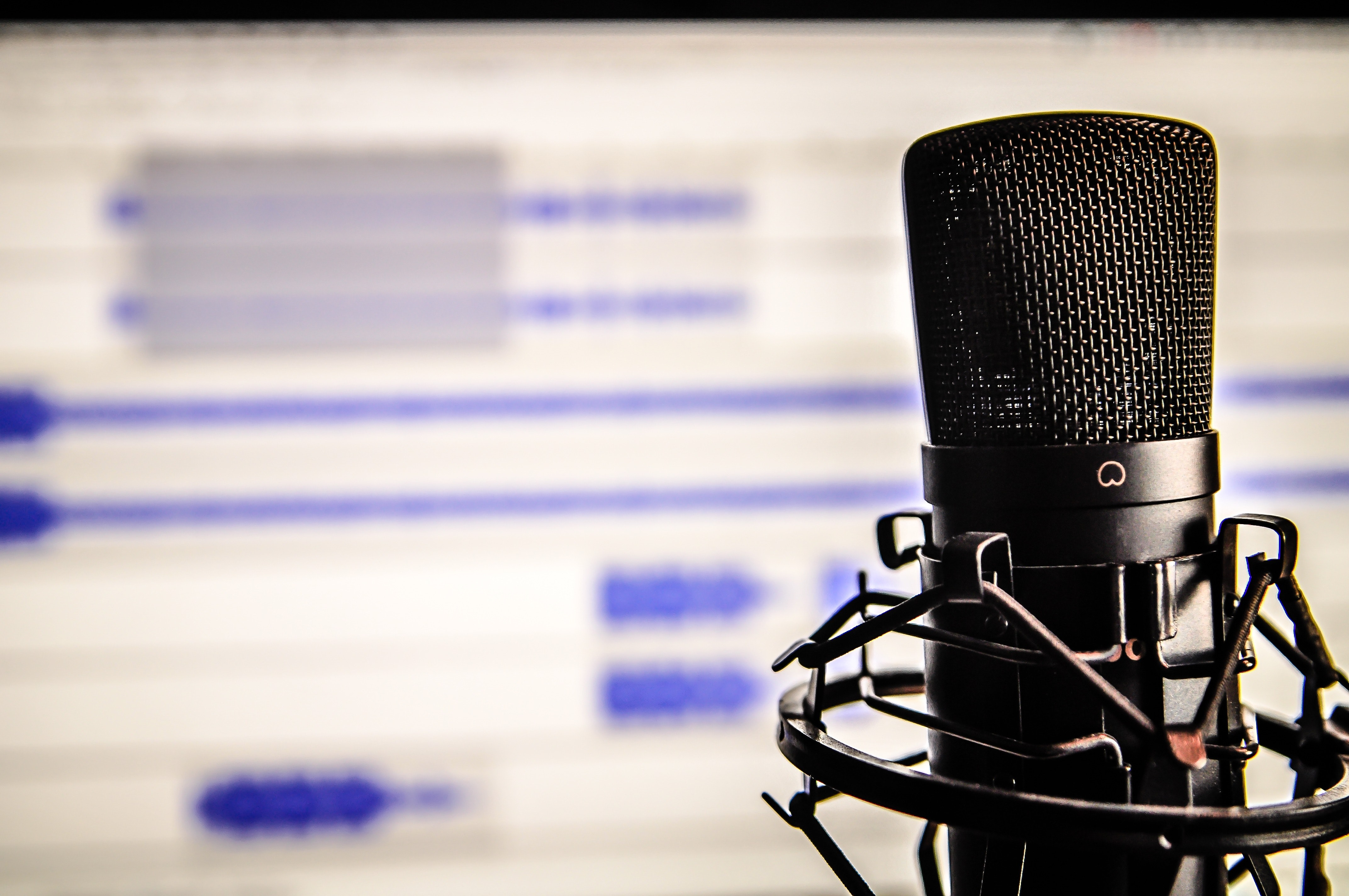 Microphone in front of desktop monitor showing audio editing program