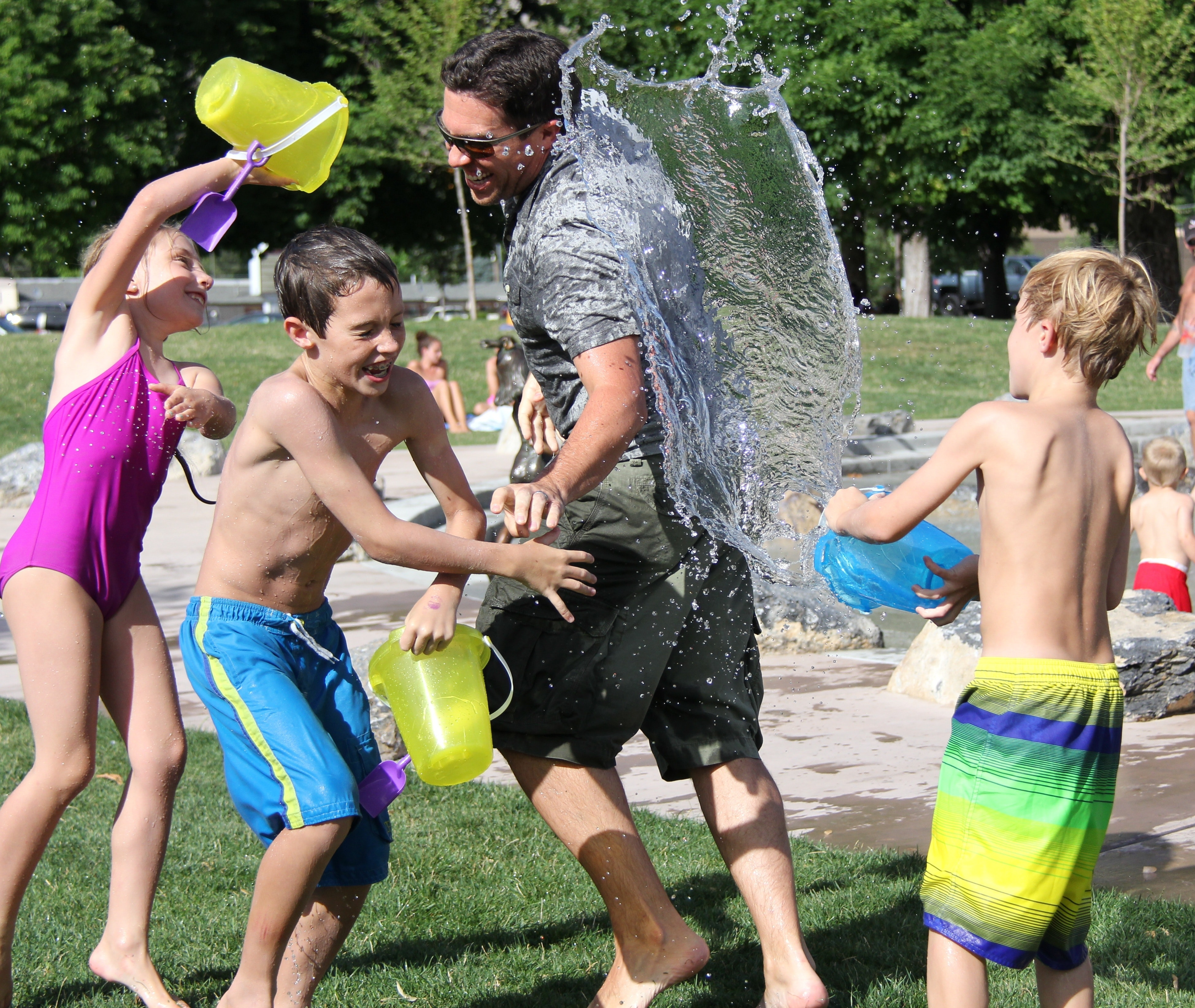 Children playing outside in water with adult staff